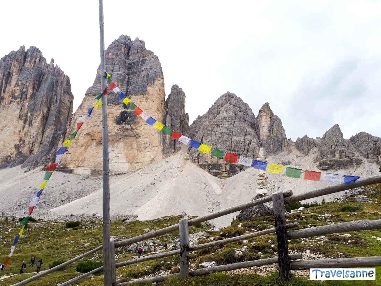 Blick auf die Drei Zinnen mit tibetischen Gebetsfahnen bei der Lange Alm
