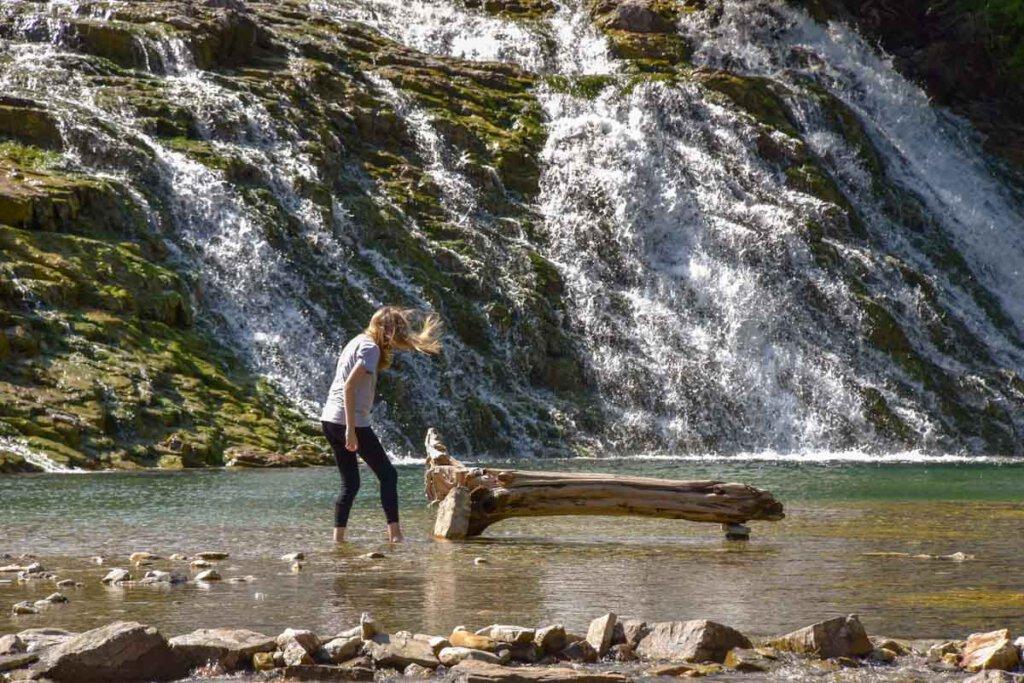 Unsere Tochter mit Wanderleggings beim Füße abkühlen im kanadischen Gebirgsfluss