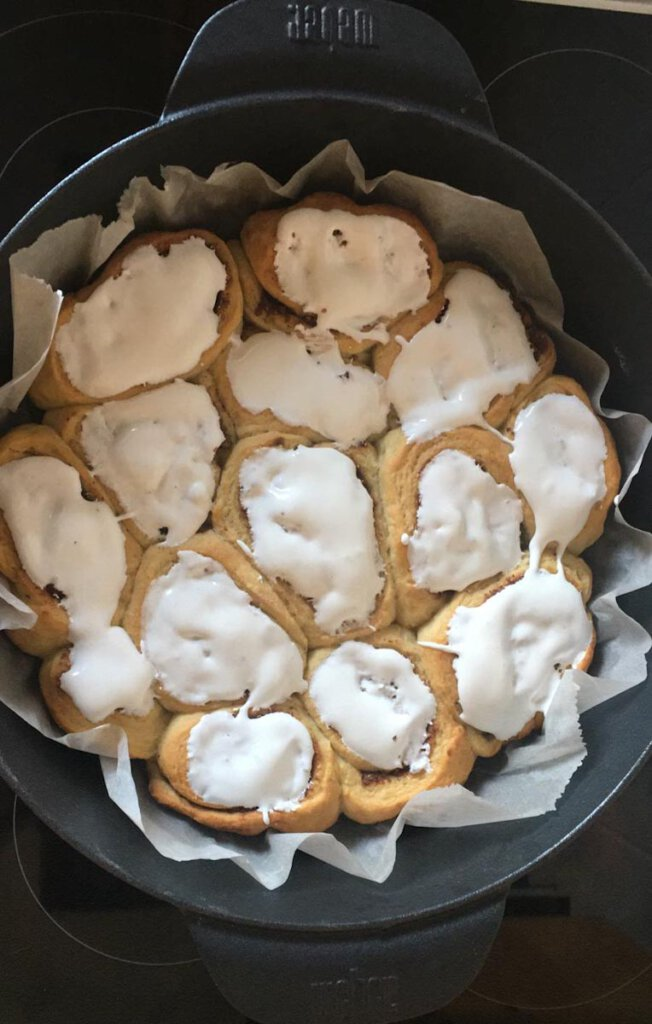 Die fertigen Zimtschnecken aus dem Dutch Oven mit dickem Frosting